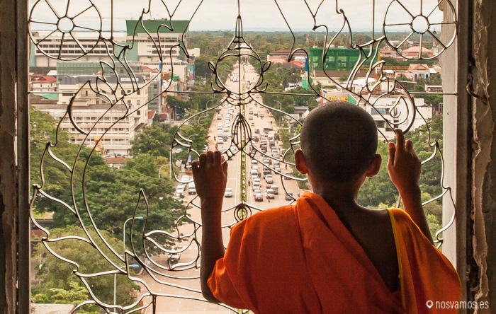 Un joven monje mirando la avenida Lane Xang desde el interior del arco del triunfo